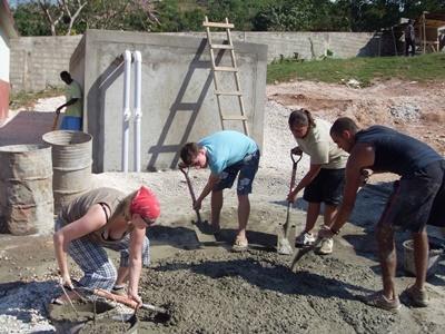 Frivillige blander sement for å bygge en bygning på byggeprosjektet på Jamaica