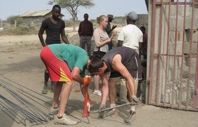 Frivillige som bærer materialer for byggeprosjektet i Tanzania