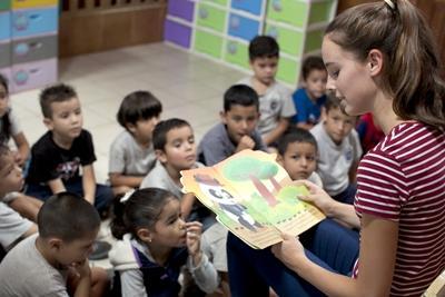 Frivilligjente leser for en gruppe barn i Kambodsjap
