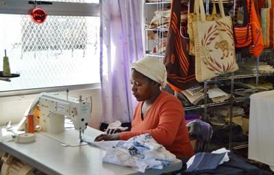 Kvinne syr klær i sin lille bedrift hvor våre frivillige jobber i Sør-Afrika