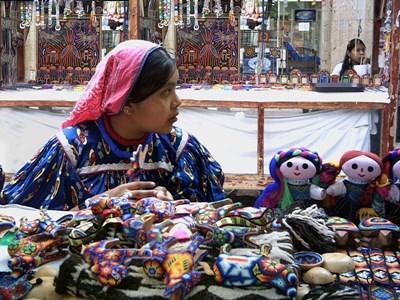 Lokal kvinne selger håndverksprodukter på et marked i Mexico