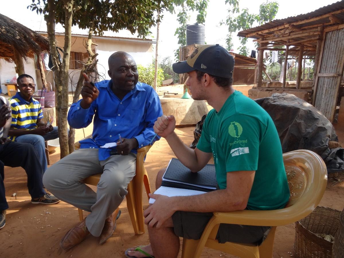 Frivillig i samtale med lokal mann på internasjonal utvikling-prosjekt i Togo