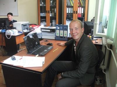Frivillig på internship sitter ved pulten sin på kontoret