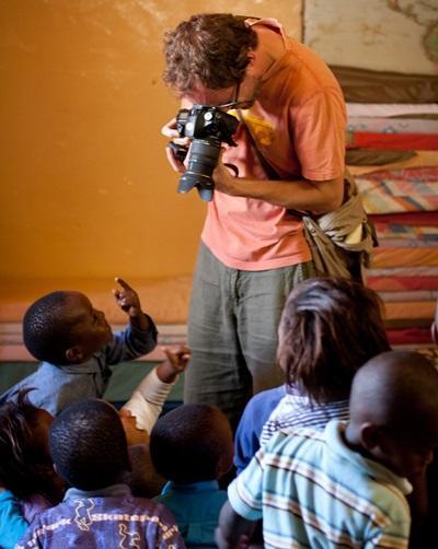 Frivillig tar bilder av barn på Rainbow Educare til artikkel