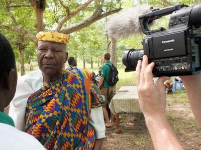 Journalistikkfrivillige intervjuer en lokal mann i tradisjonelle klær