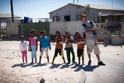 En frivillig poserer med en gruppe barn på stranda i Cape Town