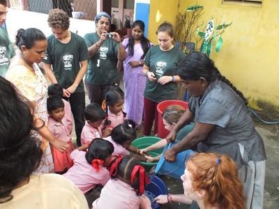 Lokale og frivillige hjelper barn med håndvask på Sri Lanka