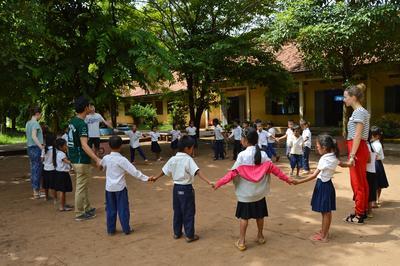Frivillige og barn i Kambodsja gjør en aktivitet i sirkel i Kambodsja
