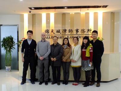 Frivillig og ansatte står foran firmaets logo på juss-internship i Kina