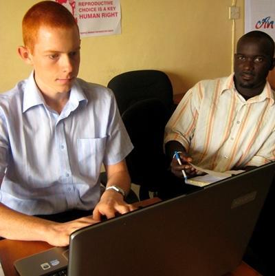 Frivillig på menneskerettighetsprosjektet i Ghana gjør kontorarbeid sammen med en ansatt