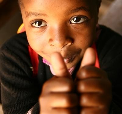 Barn gir tommelen opp til en frivillig i Tanzania
