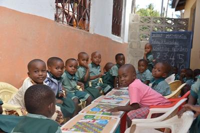 Barn som sitter rundt et bord og spiser mat på utsiden av skolen på et av Projects Abroads prosjekter med barn og ungdom