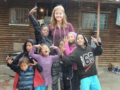 Frivillig jente sammen med lokale barn utenfor et hus i Lavender Hill township
