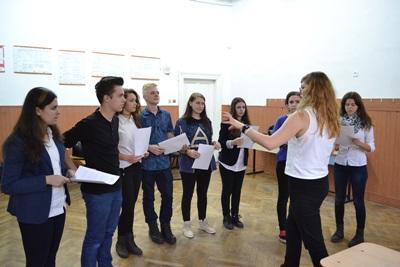 En gruppe ungdommer hører på en frivillig dramalærer i Romania