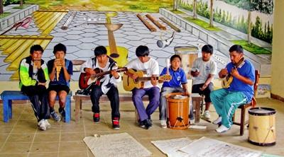 Barn i Bolivia danner et band under en musikktime ledet av en frivillig på musikkprosjektet