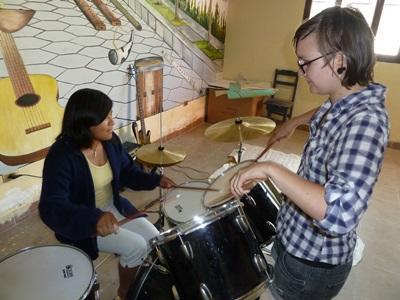 Lokal jente lærer å spille trommer med hjelp fra en frivillig i Bolivia