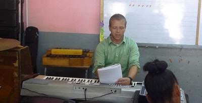 Frivillig gir en pianotime til en student på musikkprosjektet på Jamaica