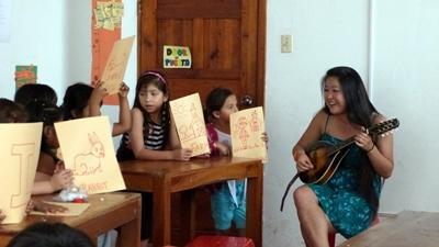 Frivillig på kunstprosjektet i Ecuador spiller gitar for skolebarn