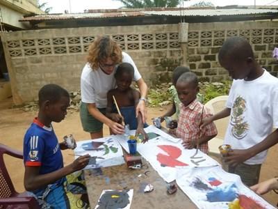 Frivillig maler utendørs med barn på landbruk- og lokalsamfunnprosjektet i Togo