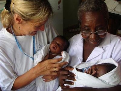 Frivillig og ansatt behandler babyer på barsel- og fødeavdelingprosjektet i Ghana