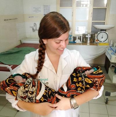 Frivillig jente med to nyfødte barn i armene på et sykehus i Tanzania