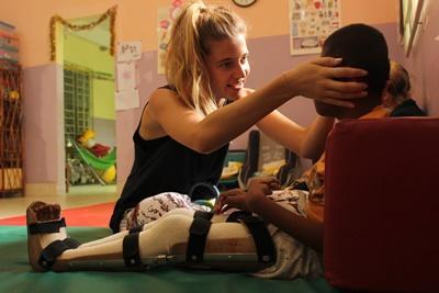 En Projects Abroad-frivillig på ergoterapi gir en ung gutt behandling på Filippinene