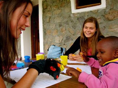 To frivillige på ergoterapiprosjekt jobber med en ung jente