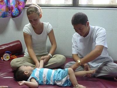 Frivillig som arbeider med en lokalt ansatt under behandlingen av et barn på ergoterapiprosjektet i Vietnam
