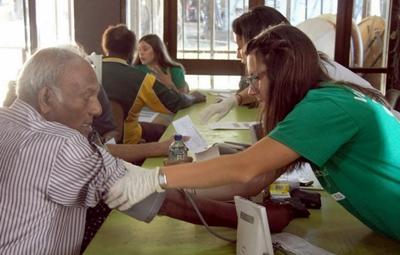 Frivillig på et Ernæringsprosjekt undersøker helsen til lokale for å lære dem om viktigheten av en sunn livsstil