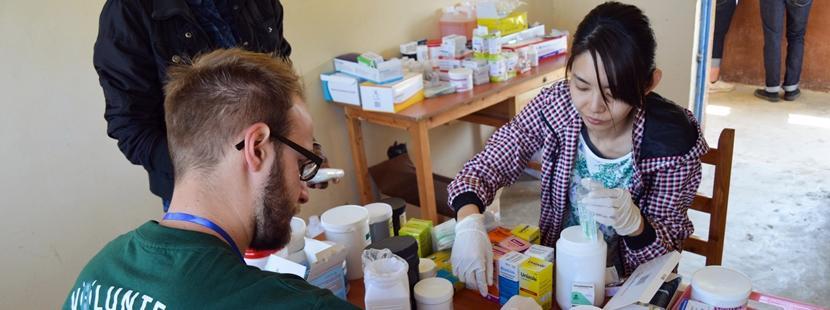 Frivillig deler ut medisiner på et farmasiprosjekt