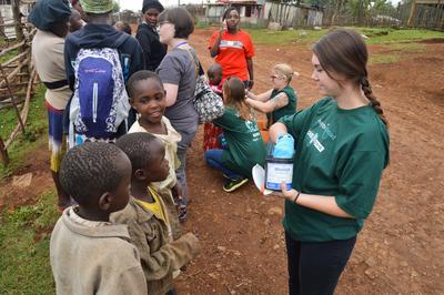 Frivillige deler ut medisiner til barn mens de deltar på oppsøkende arbeid.