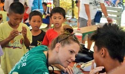 Frivillig undersøker en gutt på Folkehelseprosjektet på Filippinene
