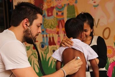Projects Abroad frivillig undersøker lungene til en ung pasient på Folkehelse i på øya Phnom Pehn i Kambodjsa