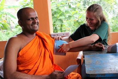 En Projects Abroad-frivillig på Folkehelseprosjektet i Sri Lanka behandler en lokal munk på en medisinsk outreach.