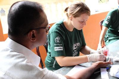 En Projects Abroad-frivillig på folkehelseprosjektet tester blodsukkeret og blodtrykket på en pasient på en outreach i hovstaden Colomobo, Sri Lanka.