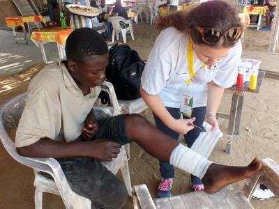 En frivillig setter på bandasje etter å ha stelt et sår på foten til en ung mann.