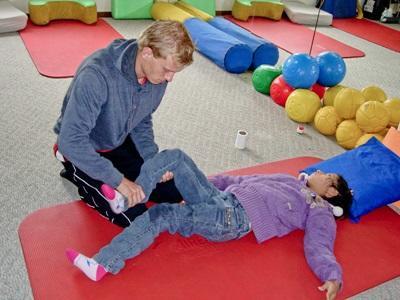 En frivillig hjelper til med behandling innen fysioterapi med et barn i Bolivia