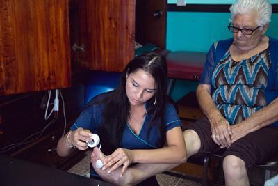 Frivillig hjelper eldre pasient med behandling av føttene i Costa Rica