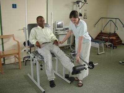 Fysioterapistudent som hjelper en mann med benproblemer på en klinikk i Ghana