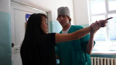 Student på fysioterapiprosjektet i Mongolia som undersøker en pasient