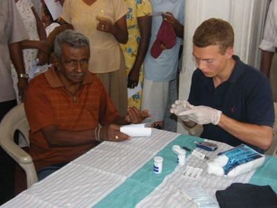 Frivillig som behandler en eldre mann på fysioterapiprosjektet på Sri Lanka, Asia