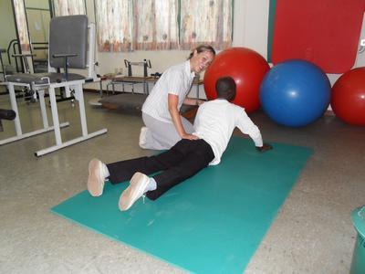 Frivillig gjør øvelser sammen med en pasient ved sykehuset