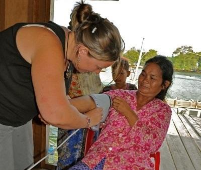 Frivillig som sjekker blodtrykket på en dame på medisinprosjektet i Kambodsja