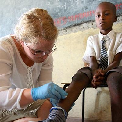 Medisinfrivillig i Kenya bandasjerer en gutt på en medisinsk klinikk