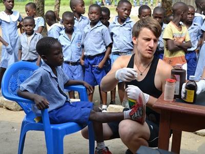 Frivillig som hjelper et barn på et Medisin- og Helseprosjekt i Ghana