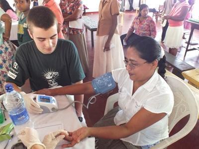 Frivillig på medisin internship som sjekker blodtrykket til en dame