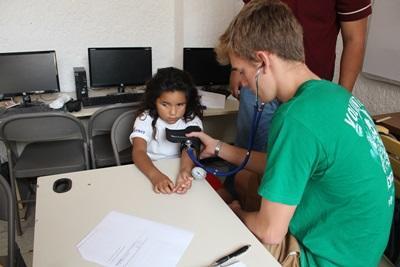 En ung gutt blir undersøkt av en frivillig på Medisinprosjektet i Mexico