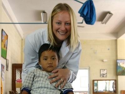 Medisinfrivillig sammen med et barn på et sykehus i Nepal