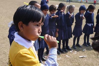 Frivillige lærer en gruppe barn å ta vare på tennene sine på et outreach i Nepal