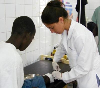 Frivillig som jobber med et barn på en klinikk på Medisinprosjektet i Senegal